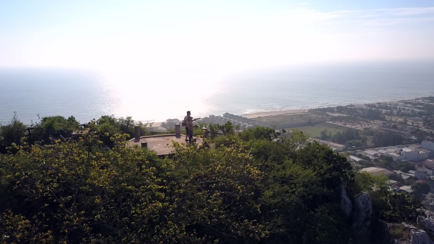 Drone removes from pictorial mountain top lookout point among trees with distant people against city at bright sun light