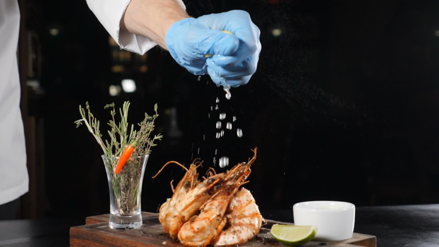 Slow motion food video. Restaurant dish serving. Lemon or lime juice dripping on flambe-style cooked shrimps put on brown board. Close up of chef hand squeezing lime . juice dribbling out of fruit. hd