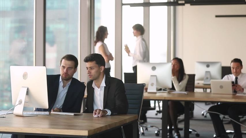 Middle eastern ethnicity and european colleagues working together using computer discuss project do task at co-working shared modern room or mentor helping new employee intern learn corporate program | Shutterstock HD Video #1035500033