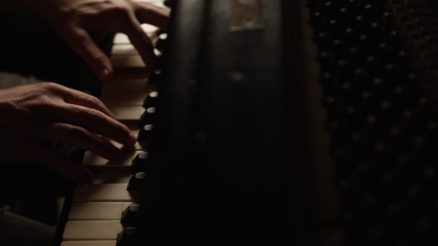 Hands of a male piano player on grand piano in low key light | Shutterstock HD Video #1035510113