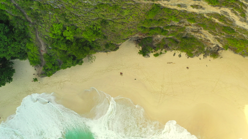 Happy couple enjoy honeymoon vacation on Kelingking Beach on background amazing nature landscape. 4K Aerial view with smooth distance from the people. Inodnesia, Nusa Penida | Shutterstock HD Video #1035518483