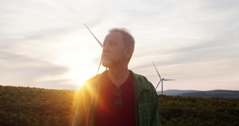 Outdoor portrait attractive man staying at sunset in gorgeous rural landscape meadows with windmills. Wind power station generating cheap electricity.   Shutterstock HD Video #1035557633