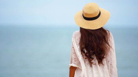 Woman with long brown hair, a lacey white beach coverup, and floppy straw? hat walks toward the incoming tide.