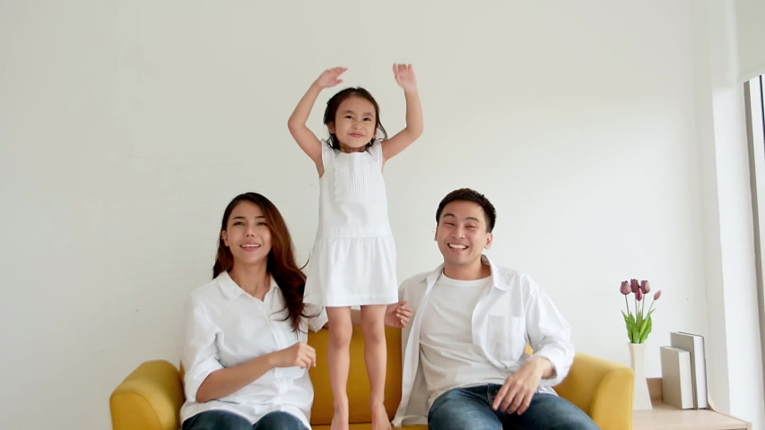 Happy Asian family watching TV together at home. Father, mother and daughter aged three glad with television. slow motion 120 fps | Shutterstock HD Video #1035588833