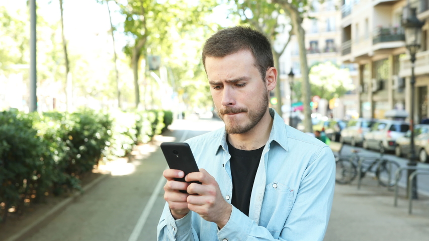 Nervous man using smart phone and looks at camera in the street | Shutterstock HD Video #1035636773