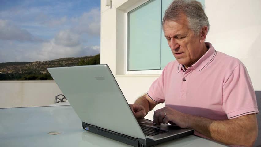 Senior man surfing on internet outside the house