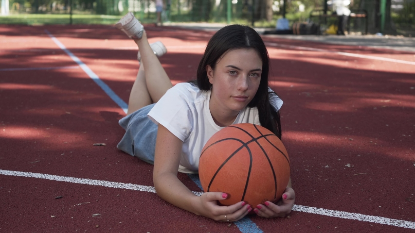 Adorable teen brunette girl with a basketball ball looking at the camera lying on the basketball court outdoors. Concept of sport, power, competition, active lifestyle. Sports and recreation. | Shutterstock HD Video #1035724793