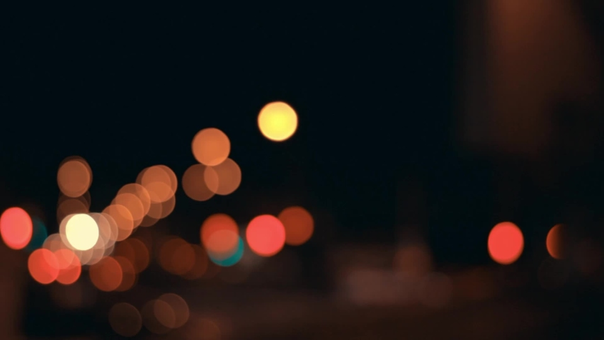 Lights of the night city background. Defocus headlights of moving cars urban traffic. Abstract bright blured colored bokeh. | Shutterstock HD Video #1035789473