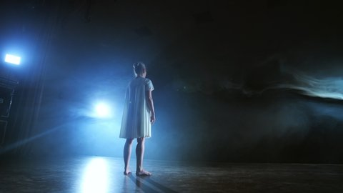 A woman in a white dress is dancing on the stage the dramatic dances of modern ballet. A ballet dancer moves plastic performing modern choreography in smoke