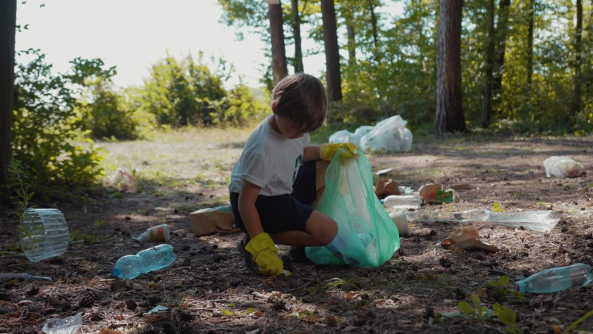 Close up voluteers activists child in gloves tidying up rubbish in park or forest save environment stop plastic pollution bag bottle recycle ecology garbage nature altruism care clean slow motion | Shutterstock HD Video #1035821453
