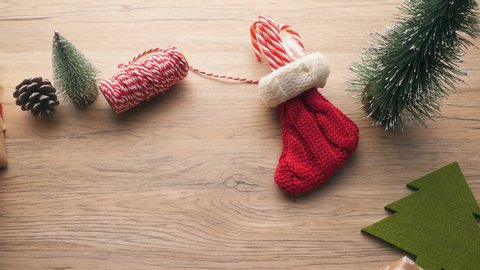 panning of christmas ornament decoration item,red sock,canndy,pine cone,christmas tree,gift box on brown wood table