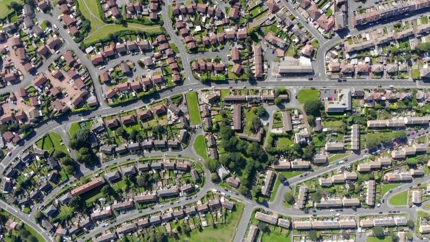 Aerial footage of the British town of Middleton in Leeds West Yorkshire showing typical suburban housing estates with rows of houses, taken on a bright sunny day using a drone.  | Shutterstock HD Video #1035910313