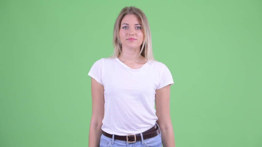 Happy young beautiful blonde woman smiling with arms crossed | Shutterstock HD Video #1035919793