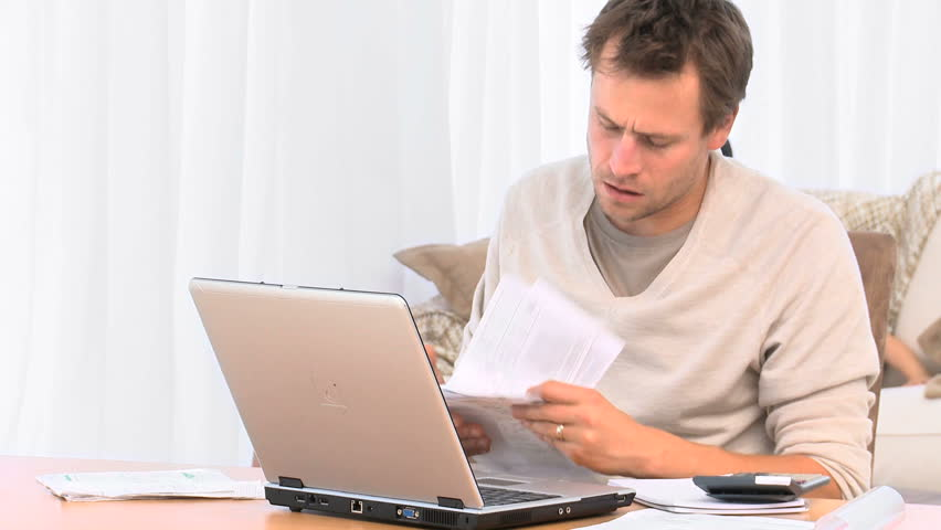 Annoyed guy calculating bills on the laptop