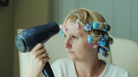Woman with curlers on her head dries hair with a hairdryer