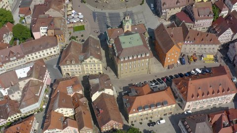 Aerial view of the city Schwäbisch Hall in Germany on a sunny day. Tilt up from city hall to the church.