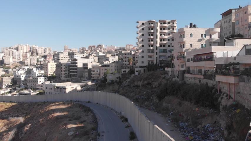 Flying close to security fence in Jerusalem Drone flight view of east Jerusalem security wall divide between Israeli and Arab neighborhood  Anata and pisgat zeev, israel  | Shutterstock HD Video #1036098413