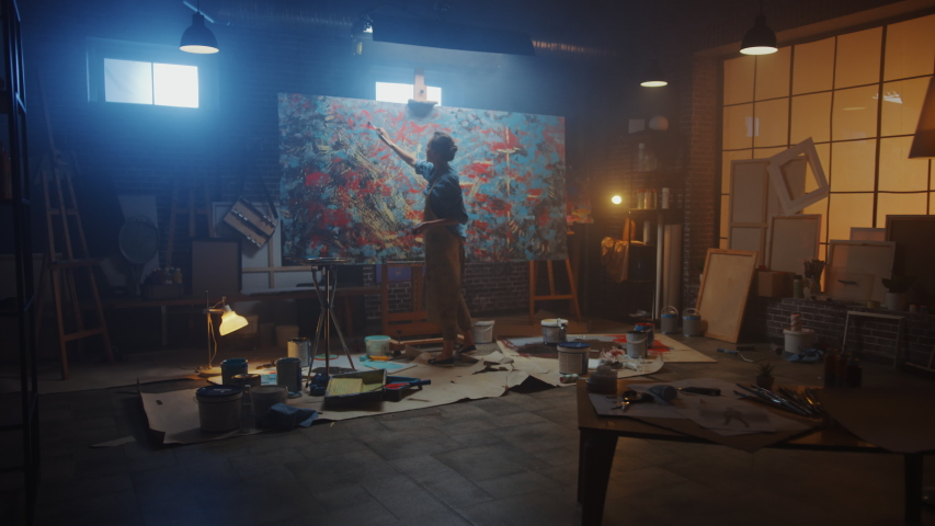 Talented Female Artist Works on Abstract Oil Painting, Using Paint Brush She Creates Modern Masterpiece. Dark and Messy Creative Studio where Large Canvas Stands on Easel Illuminated. Zoom out #1036107533