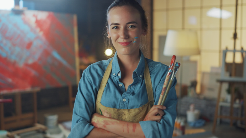 Young Female Artist Dirty with Paint, Wearing Apron, Crosses Arms while Holding Brushes, Looks at the Camera with a Smile. Authentic Creative Studio with Large Canvas. Head and Shoulders Portrait | Shutterstock HD Video #1036107653