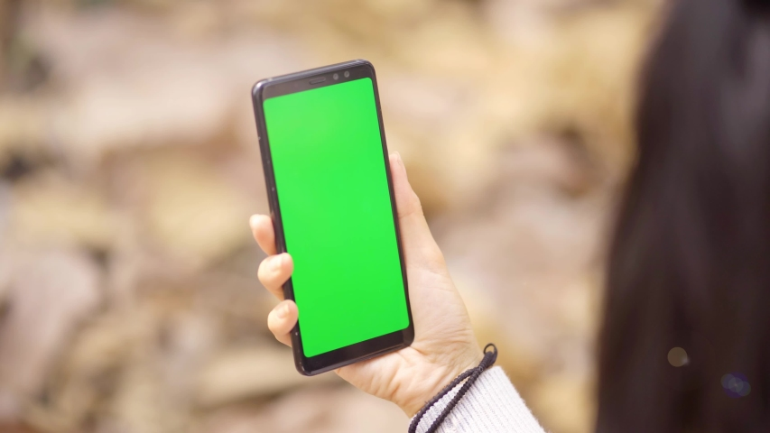 Closeup of woman hand holding a mobile phone with empty green screen at the autumn park. Shot in 4k resolution | Shutterstock HD Video #1036156433