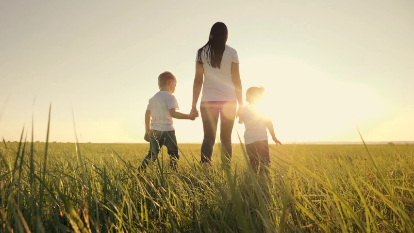 A happy family. Mom with children walks on a green field at sunset. Traveling and walking outdoors. The concept of happiness and health. Teamwork | Shutterstock HD Video #1036173143