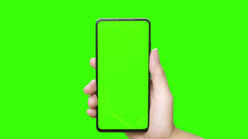 Man's hand holding a mobile telephone with a vertical green screen in tram chroma key smartphone technology cell phone touch message display hand with luma white and black key | Shutterstock HD Video #1036222223