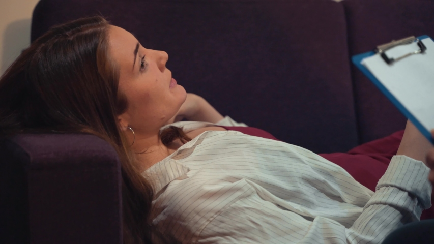 Psychologist listening to young depressed female patient lying on sofa and writing notes, mental health and counseling. Psychological treatment concept | Shutterstock HD Video #1036318403