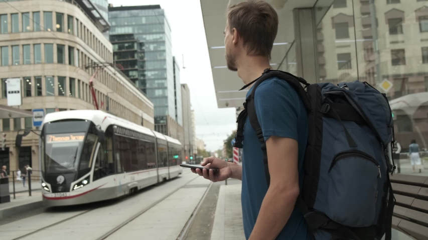 Millennial man tourist with backpack and smartphone stand on public transport stop and waiting tram in modern city center. Travel concept. | Shutterstock HD Video #1036327883