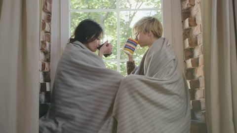 Attractive lesbian couple wrapped in blankets sitting on windowsill, drinking coffee and enjoying time together
