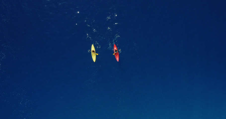 Aerial view of two kayakers paddling together in pristine dark blue ocean water on a sunny day, young adventurous couple kayaking together