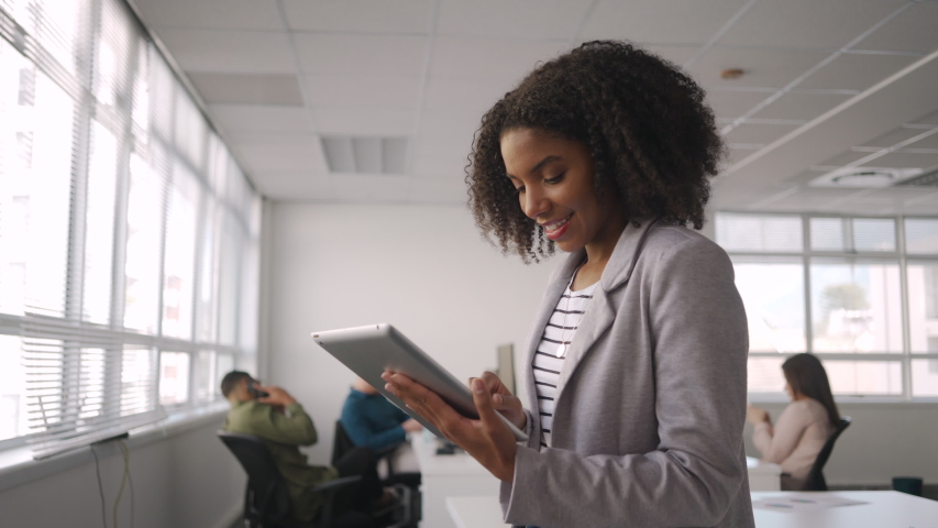 Successful smiling young african american businesswoman in grey jacket using a digital tablet in front of colleague working at workplace   Shutterstock HD Video #1036574933