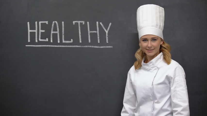Professional chief cook smiling against blackboard with health word, nutrition   Shutterstock HD Video #1036590203