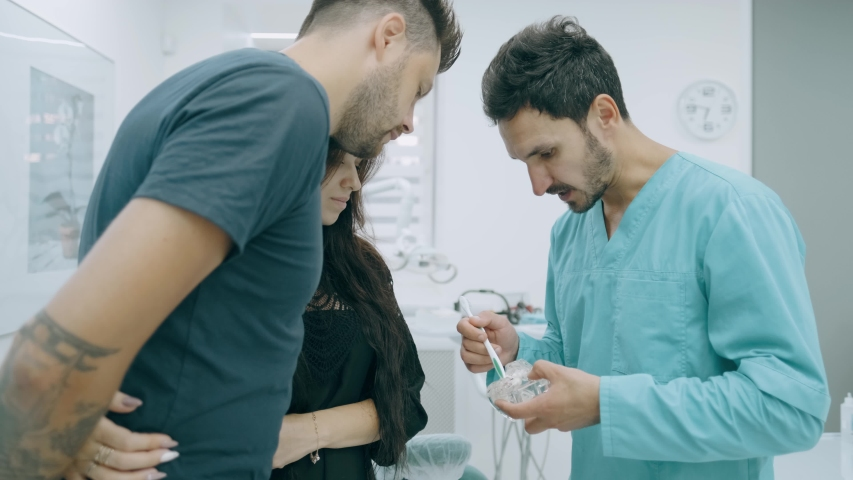 Doctor dentist is showing to happy family on a jaw model how to clean the teeth with toothbrush properly and right | Shutterstock HD Video #1036608923