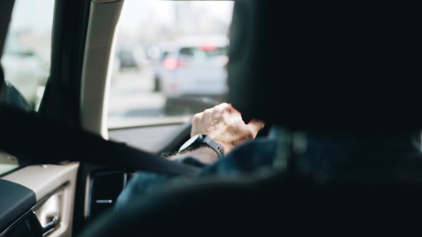 A man drives a car around the city. The view from the back seat. His hand is visible.   Shutterstock HD Video #1036700753