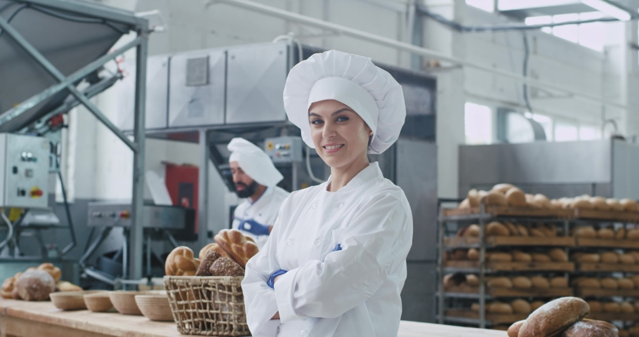 Commercial face of a amazing woman baker looking straight to the camera and smile cute background his colleague baker dancing and moving funny beside their table work. slow motions | Shutterstock HD Video #1036837673