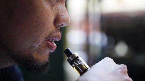 Close-up of man inhaling an e-cigarette vaping device.
