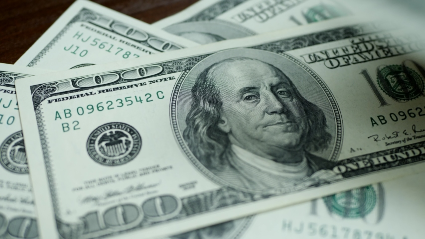 Dollar bills fall on brown wooden table. To count money or business concept. The United States one hundred-dollar  | Shutterstock HD Video #1036927313