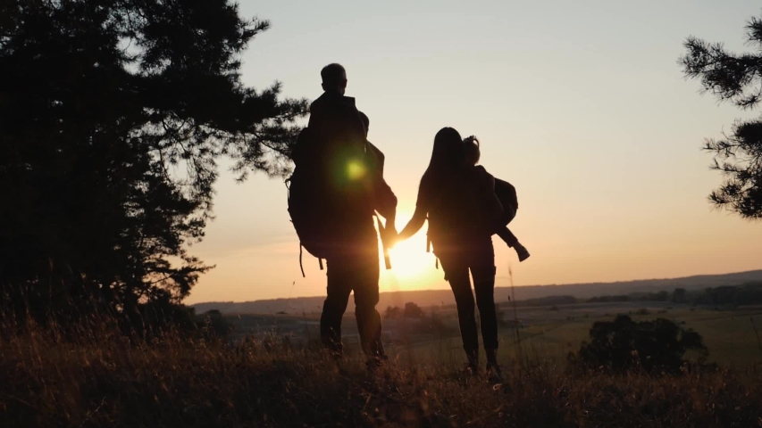 A happy family. Family travel and hiking through the forests at sunset. Walking in the open air, teamwork. Healthy lifestyle concept | Shutterstock HD Video #1036946153