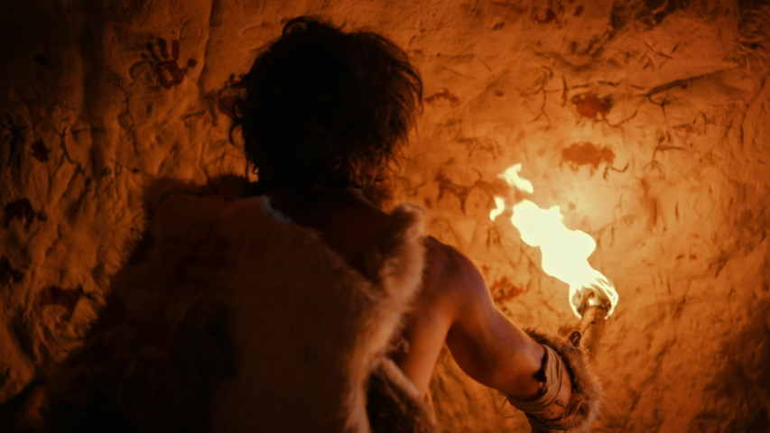 Primeval Caveman Wearing Animal Skin Standing in His Cave At Night, Holding Torch with Fire Looking at Drawings on the Walls at Night. Cave Art with Petroglyphs, Rock Paintings. Back View | Shutterstock HD Video #1037019383