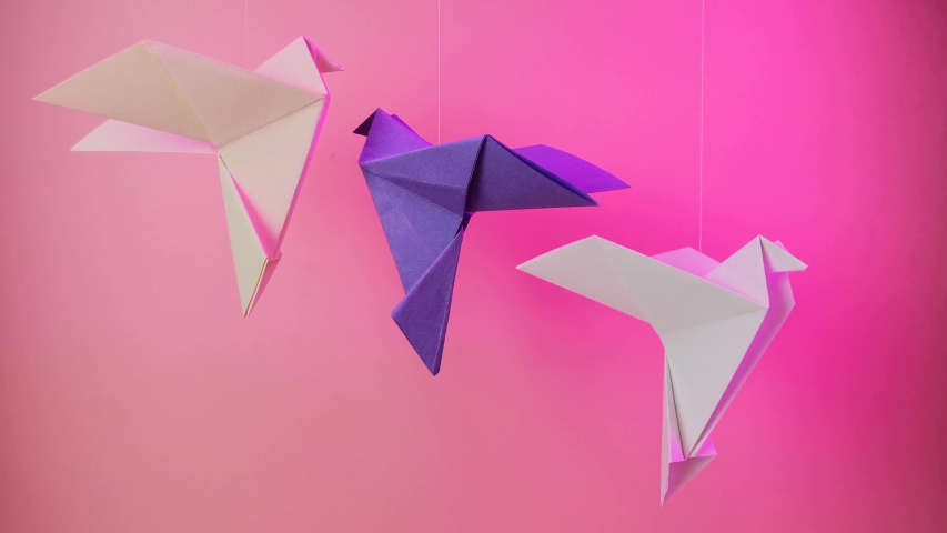 Origami paper dove on a pastel pink background. The concept of arts and crafts, activities for children. Minimalism, fly, place for text. Bright trend neon light. | Shutterstock HD Video #1037034443