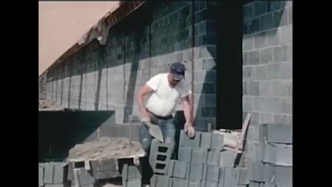 CIRCA 1950s A stonemason builds a wall, and shots of exposed concrete blocks creating a design on a building