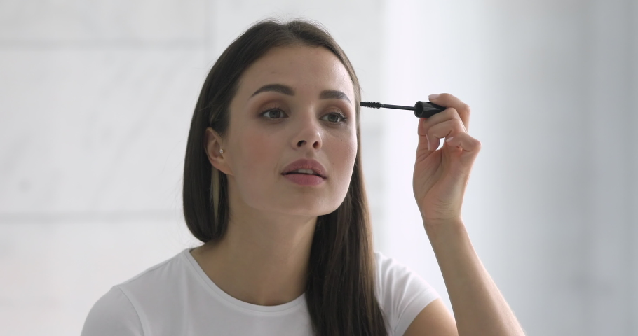 Confident happy young woman holding mascara apply on eyeleashes prepare getting ready in the morning, smiling beautiful girl doing make up put cosmetics on face looking in mirror in bathroom at home | Shutterstock HD Video #1037144993