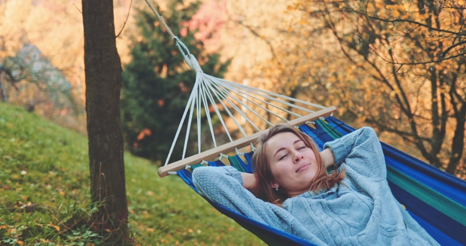 Woman Wakes Up after Sleep in a Hammock in Autumn. SLOW MOTION. Young woman daydreams, unwinds in a calm fall outdoor, rural country nature with colourful forest in background. Cozy season. | Shutterstock HD Video #1037145683