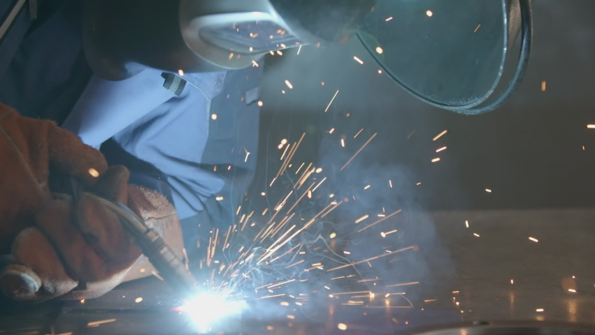 Close-up blacksmith welder in protective mask works with metal using a welding machine, bright sparks and flashes in super slow motion | Shutterstock HD Video #1037172983