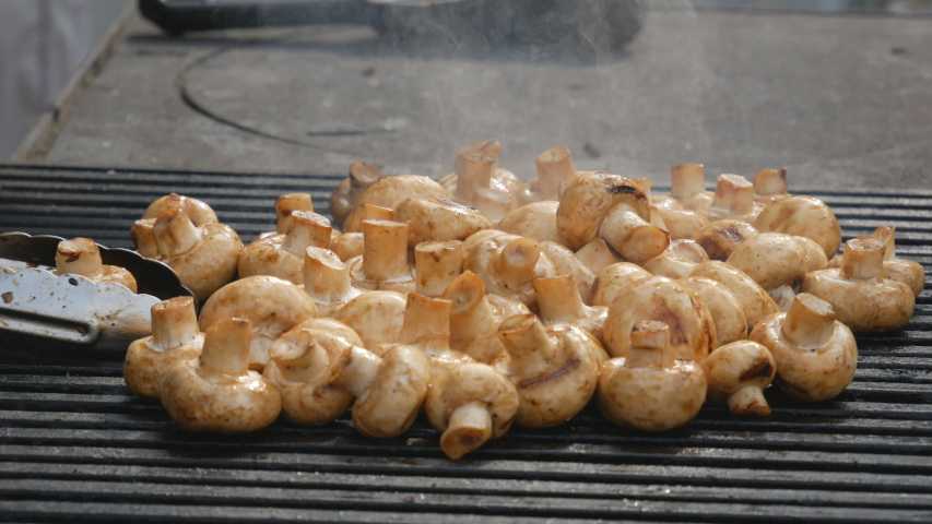 Chef's hands cooks mushrooms on the grill. Delicious, wholesome grilled food. Diet vegan barbecue. barbecue party | Shutterstock HD Video #1037174573