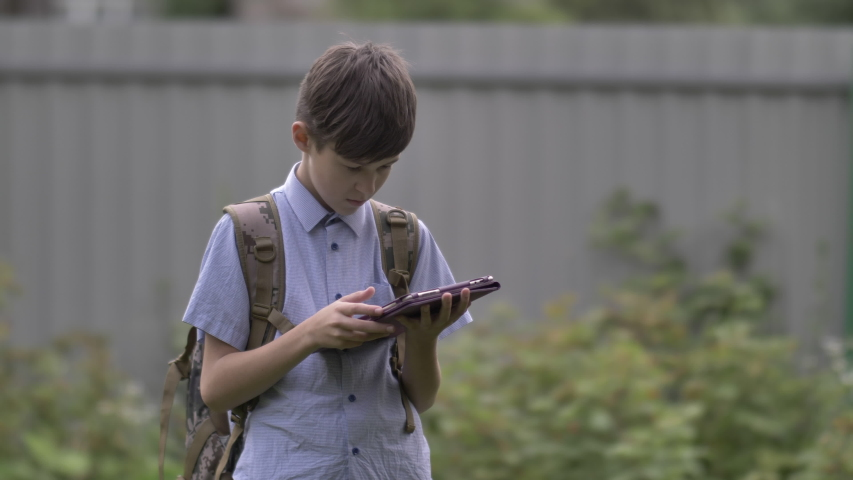 Schoolboy with backpack uses tablet outdoors | Shutterstock HD Video #1037175863