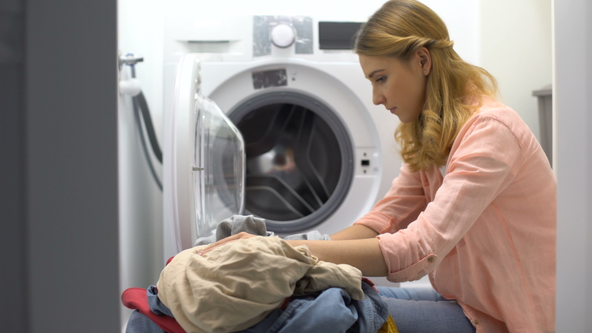 Tired woman loading clothes in washing machine, annoyed with housework routine | Shutterstock HD Video #1037180813