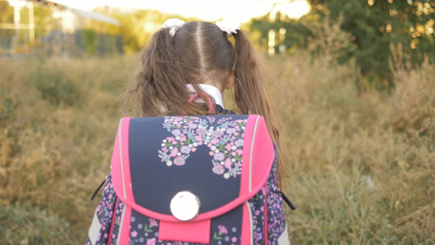 A little girl of 7 years old coming home from school with a briefcase on his shoulders, rear view. | Shutterstock HD Video #1037198783