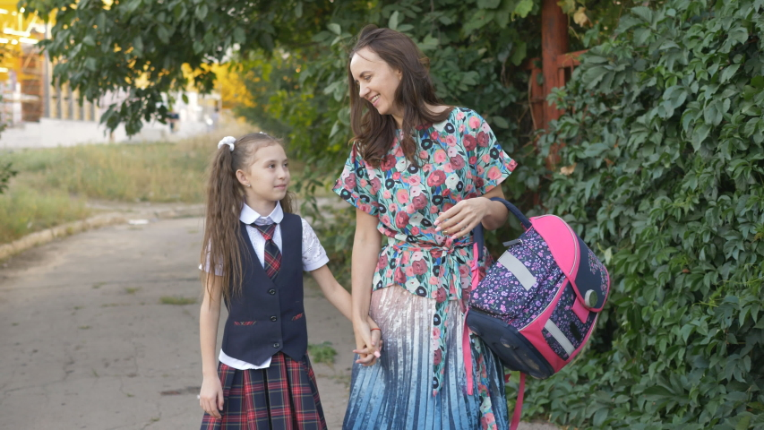 Mother and young daughter go home from school together | Shutterstock HD Video #1037200013