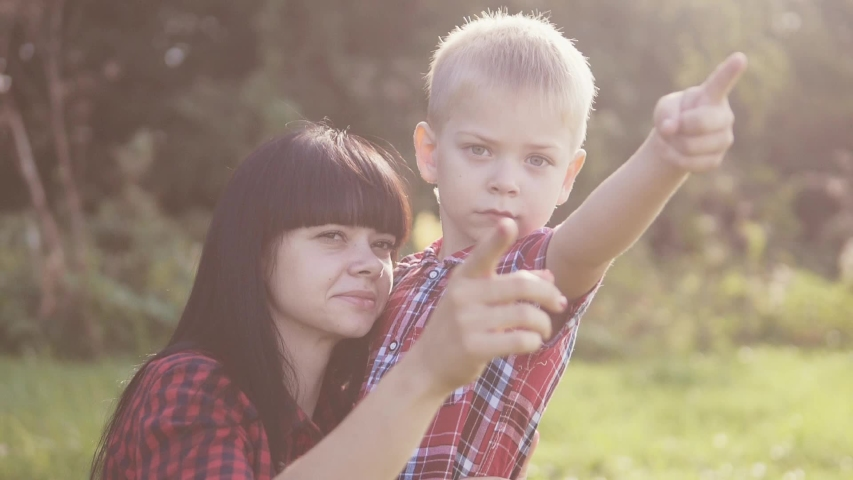 Happy family mother's day funny the nature slow motion video teamwork outdoors. son boy hugs mom girl outdoors shows the distance with his hand sunlight cute video care. mother and son cuddle friendly   Shutterstock HD Video #1037217923